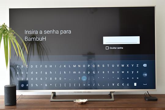 A imagem mostra o pedido para introduzir a senha da rede Wi-Fi selecionada, com um teclado virtual no ecrã do televisor.